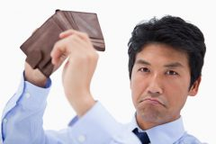 Businessman showing his empty wallet against a white background